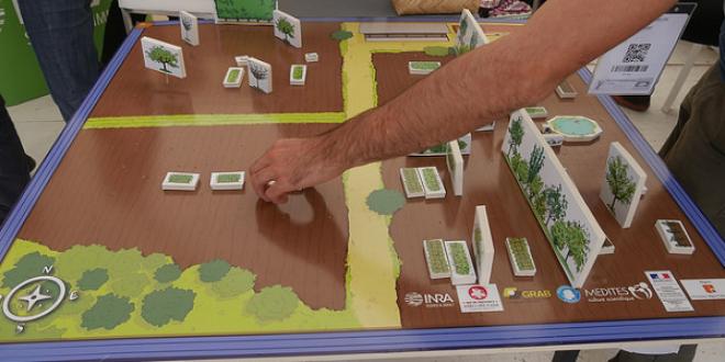 """Les visiteurs du salon Tech&Bio 2017 pouvaient jouer au jeu de plateau """"Dessinez le verger de demain"""" et échanger avec des techniciens afin d'améliorer leur système de production."""